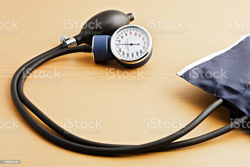 Blood pressure measuring device on wooden desk stock photo