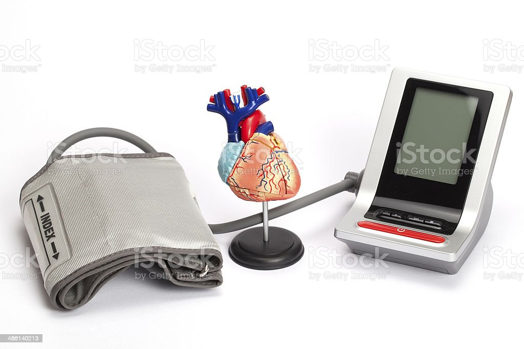 Blood pressure monitor and anatomic model of heart stock photo