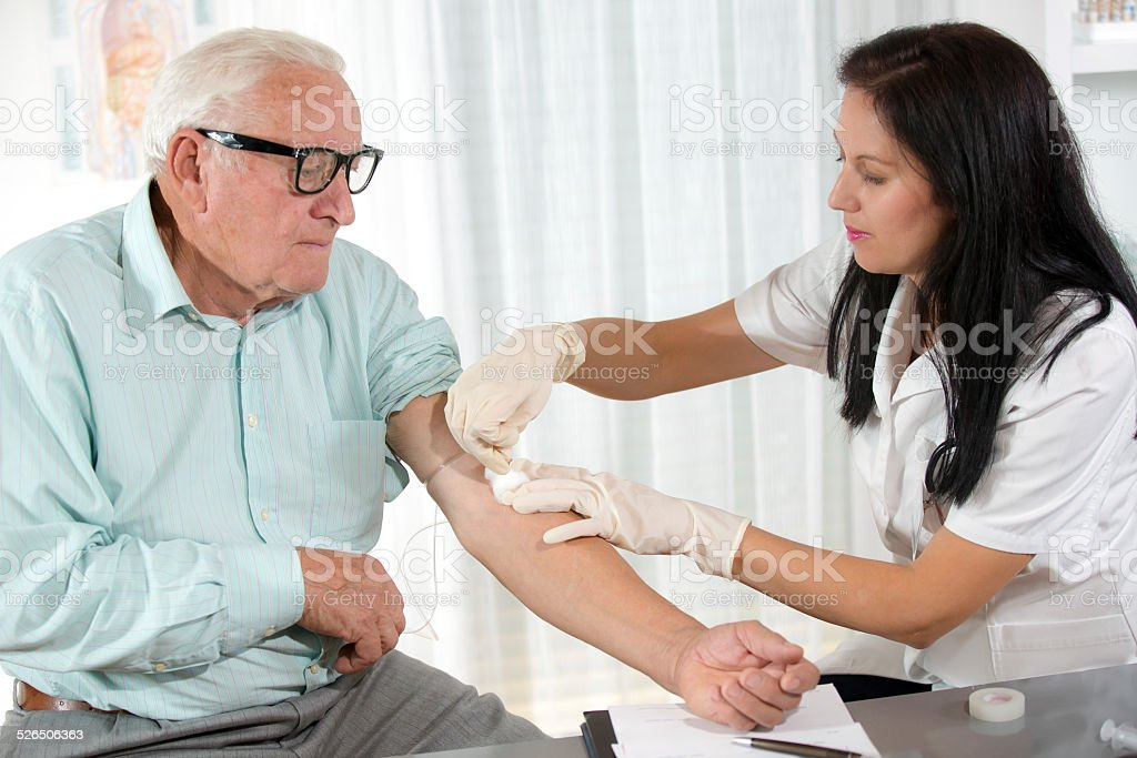 Blood sampling by an older man stock photo