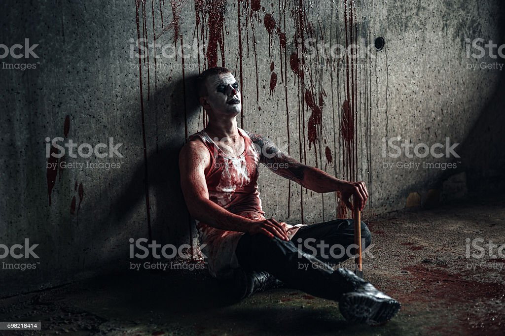 Bloody clown-maniac with ax stock photo