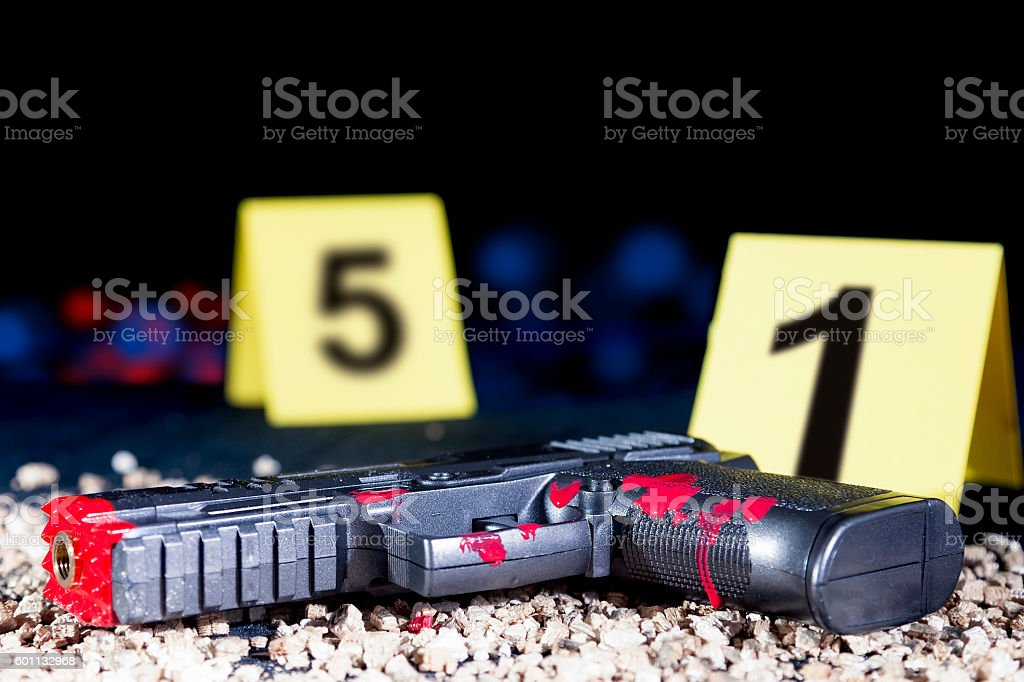 bloody gun at the crime scene in the night stock photo