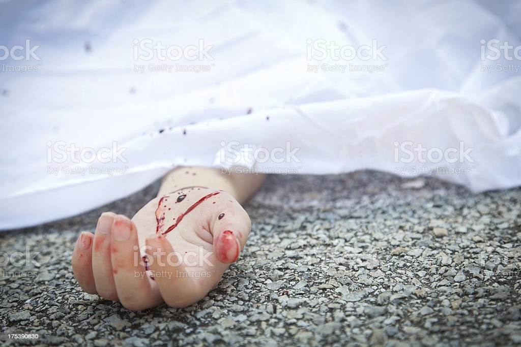 Bloody hand at an accident scene pavement stock photo
