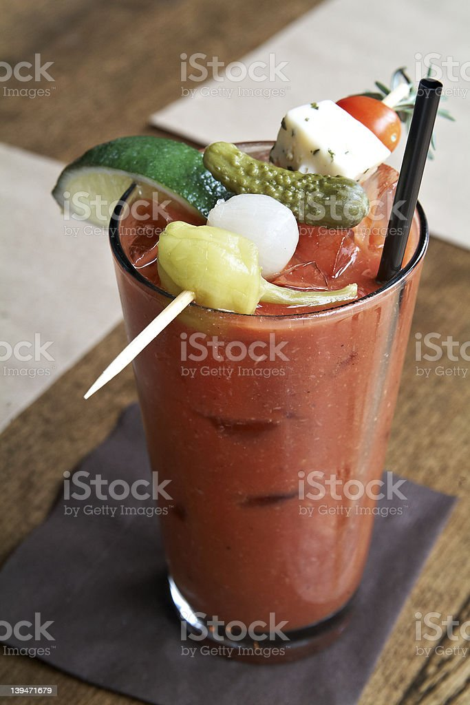 A Bloody Mary is garnished with cheese, vegetables, and lime stock photo