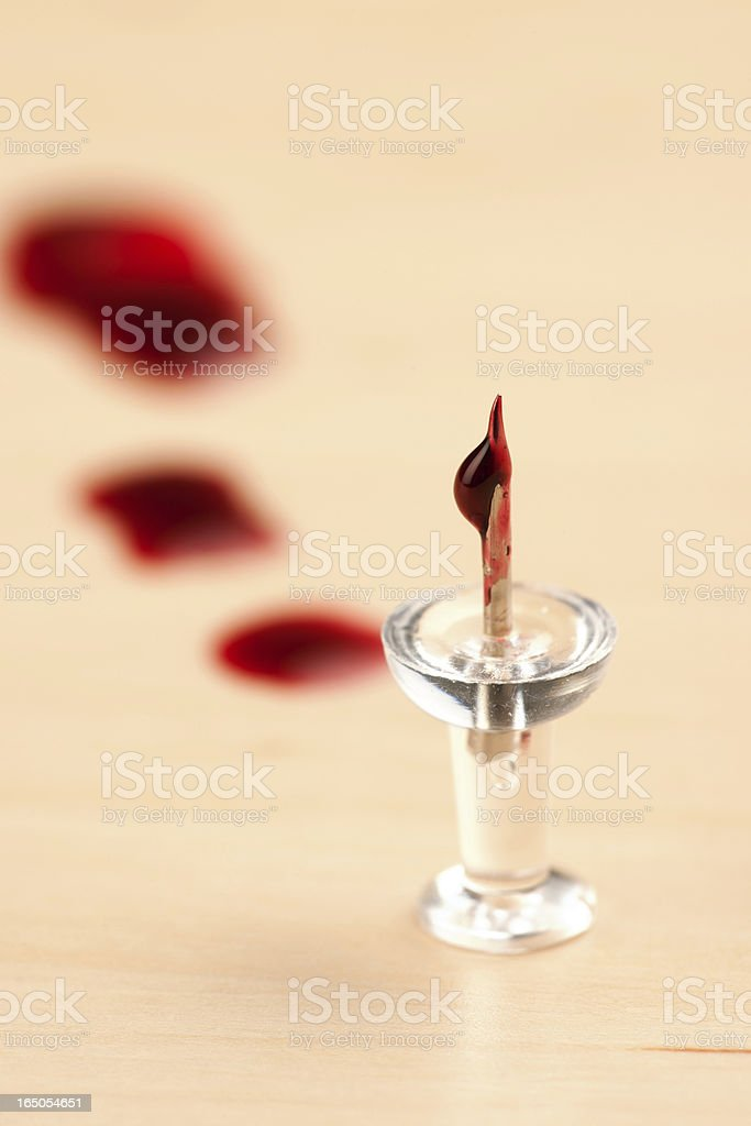 Bloody Thumbtack on Wooden Floor with Blood Trail in Background stock photo