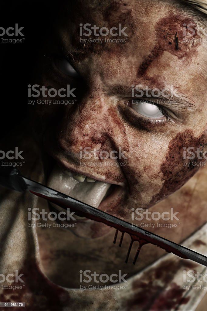 bloody zombie face with possessed white eyes licking knife stock photo