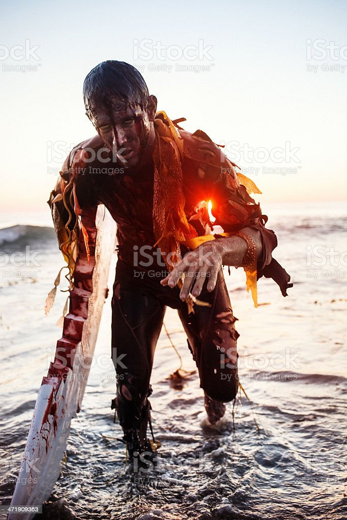 Bloody zombie with one crab hand emerging from the ocean stock photo