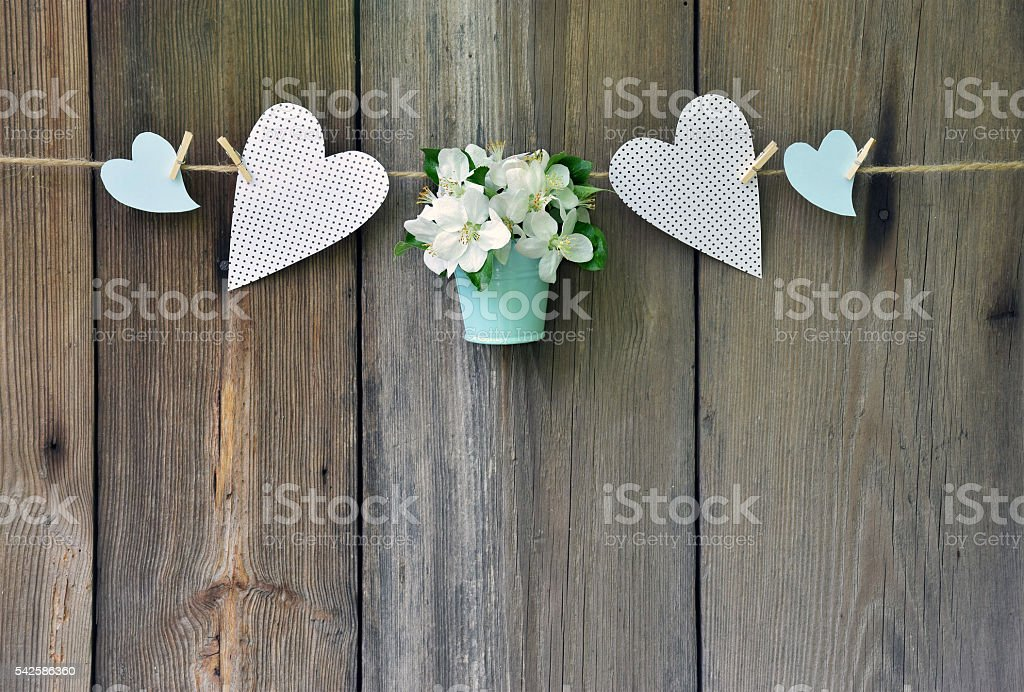 Blossoming apple in the basket and heart on wooden background. stock photo