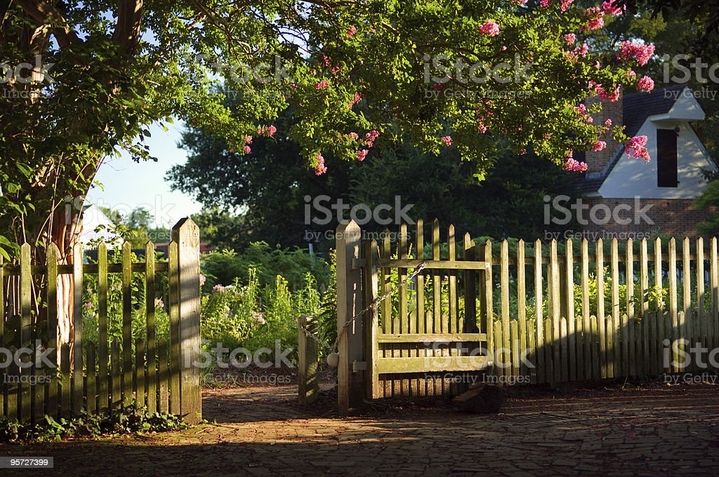 Blossoming tree with white picket fence outside of house stock photo