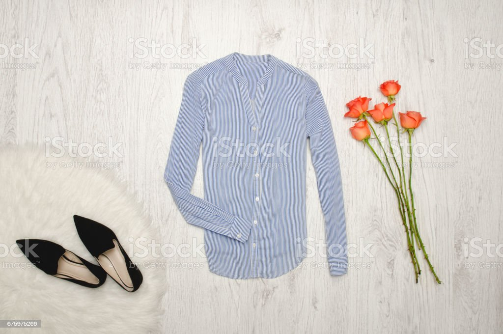 Blouse in fine stripes, shoes and orange roses on a wooden background. Fashionable concept stock photo