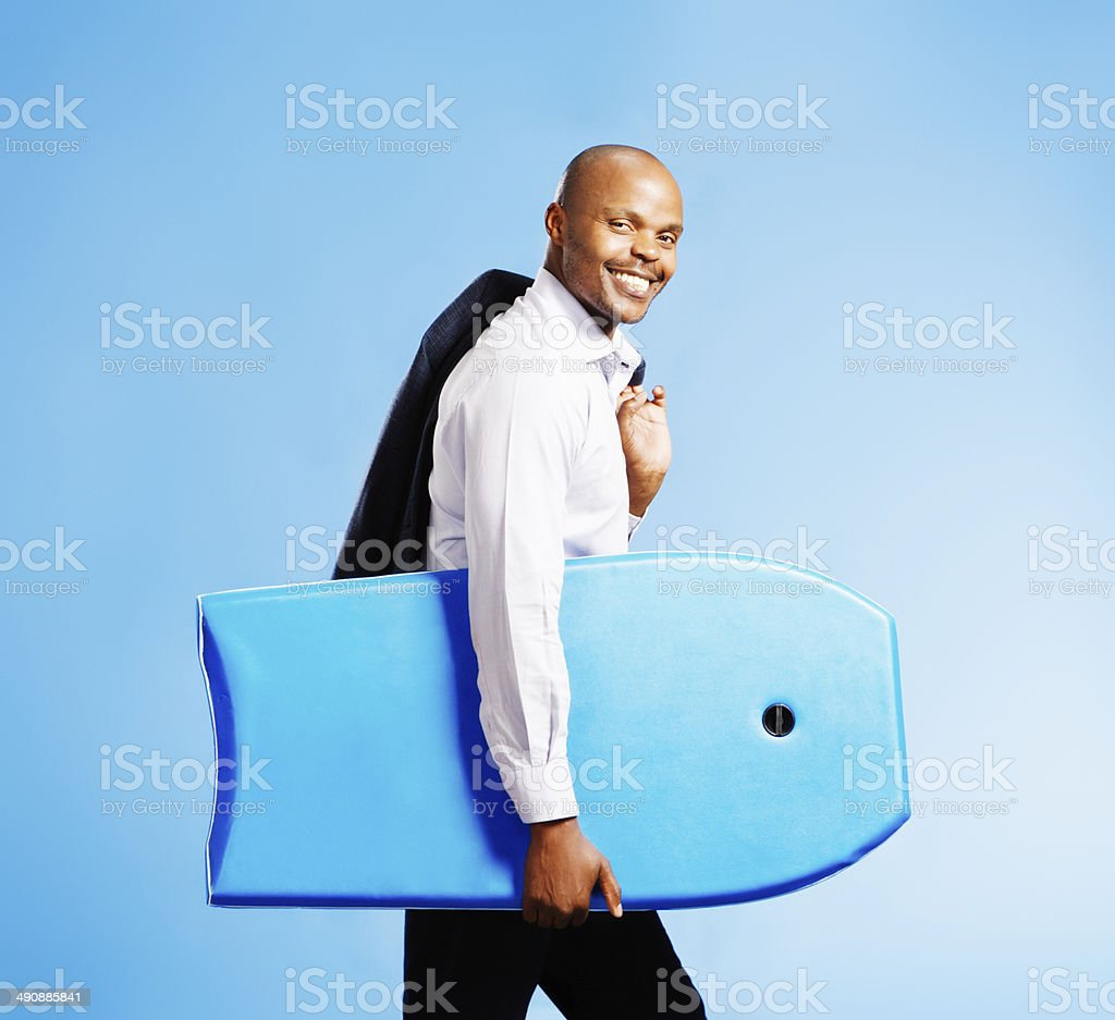Blow business, I'm off to the beach! Businessman with surfboard royalty-free stock photo