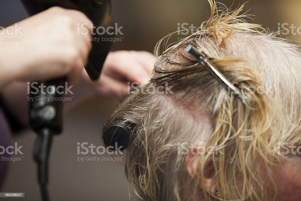 Blowdrying hair with brush and pins stock photo