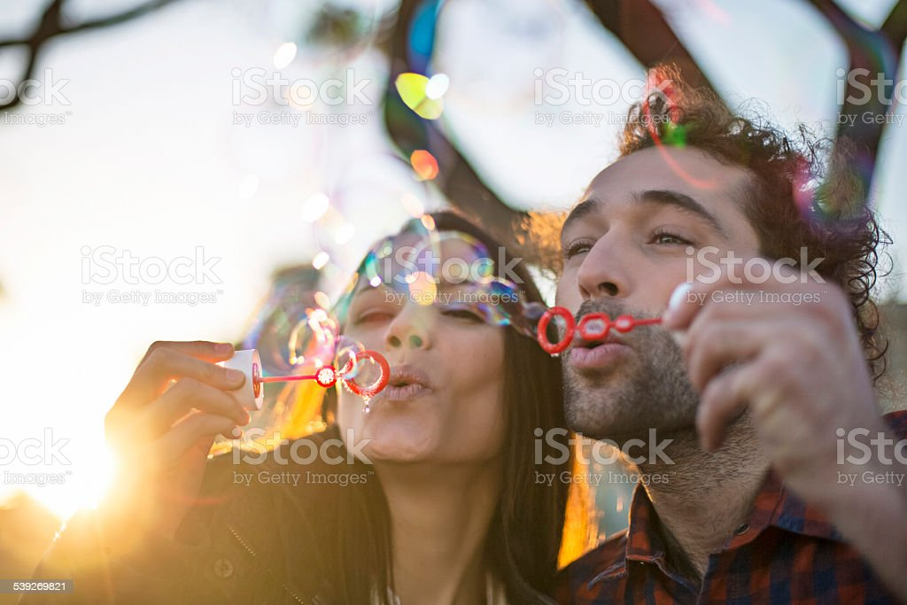 Blowing bubbles at sunset stock photo