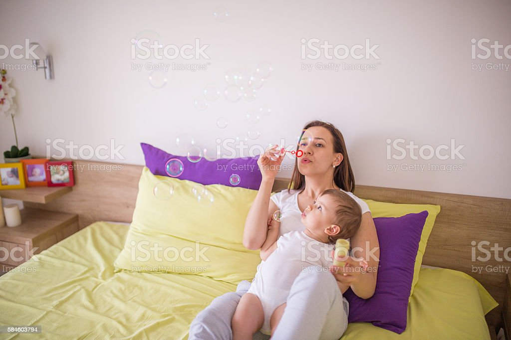 Blowing bubbles with mom stock photo