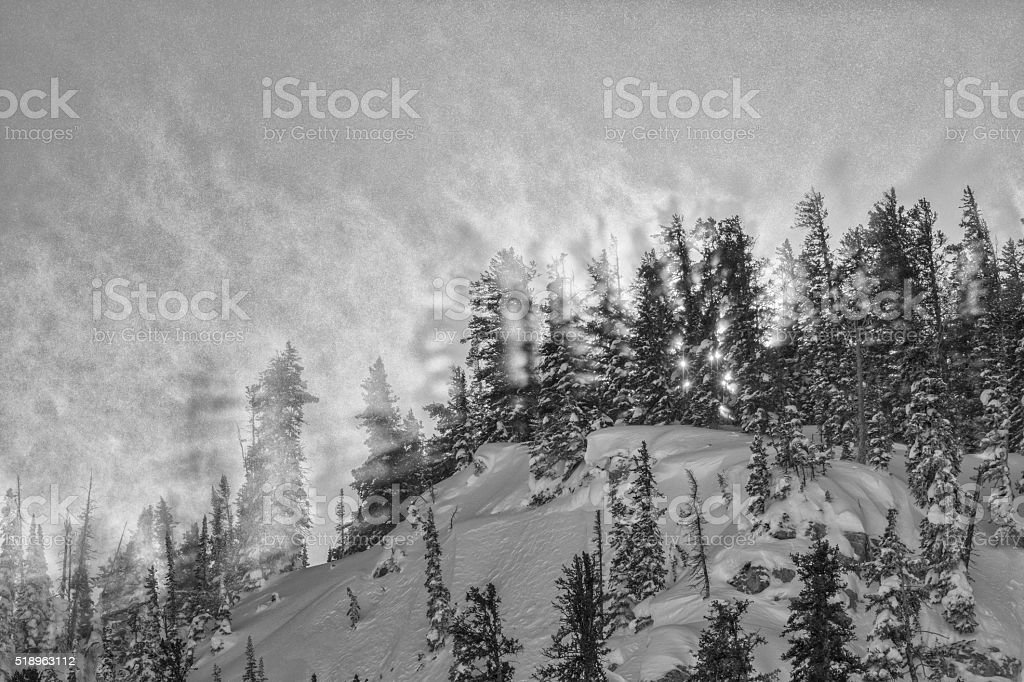 Blowing Snow lighting up on a Teton ridge monochrome. stock photo