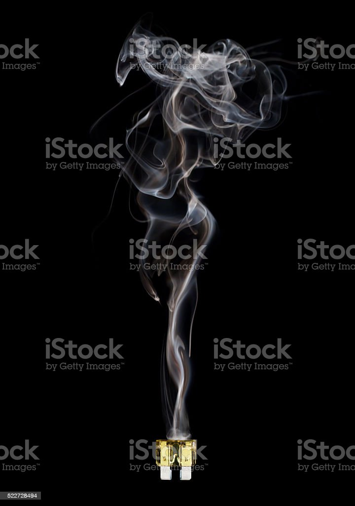 Blown automotive fuse with feminine smoke on black background stock photo