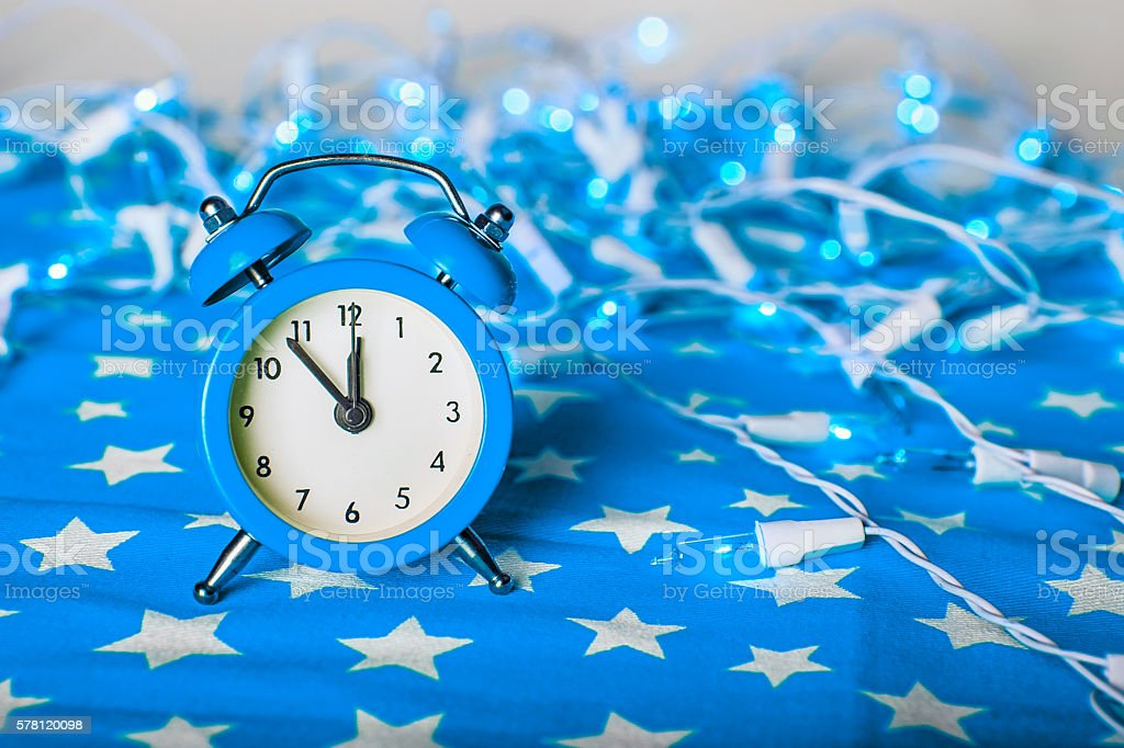 blue alarm clock with lights bokeh on blue fabric background stock photo