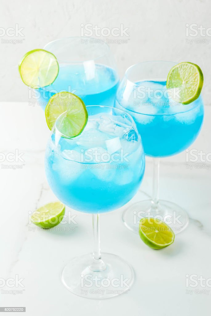 Blue alcohol cocktail with lime stock photo