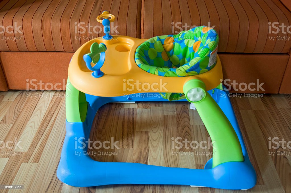 Blue and green empty baby walker on laminate floor stock photo