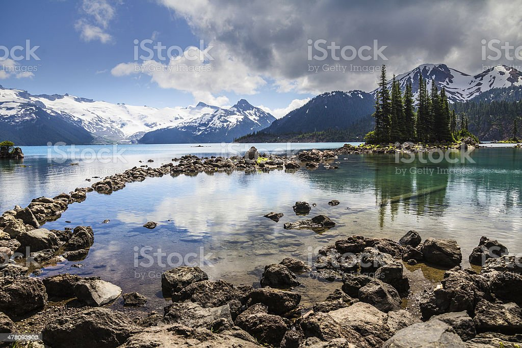 Blue and green reflections of trees and mountains, Garibaldi Lake stock photo