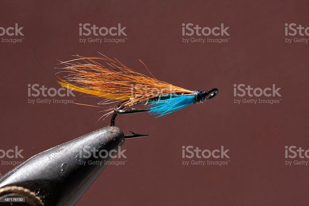Blue and orange fishing fly stock photo