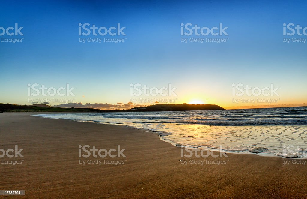 Blue and orange sunset on beach stock photo