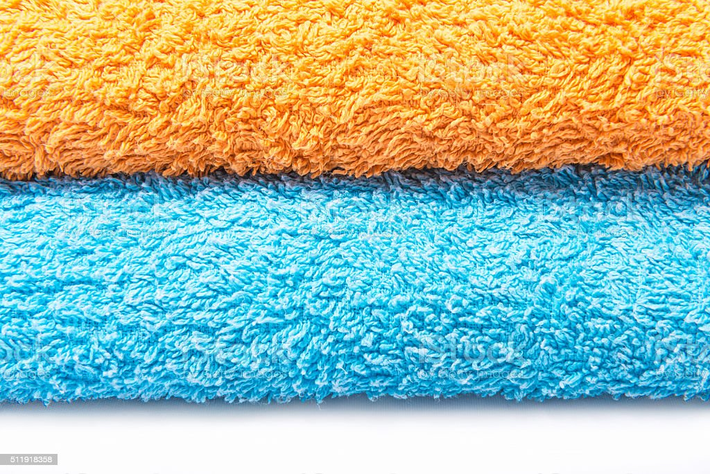 Blue and orange towels on a white background stock photo
