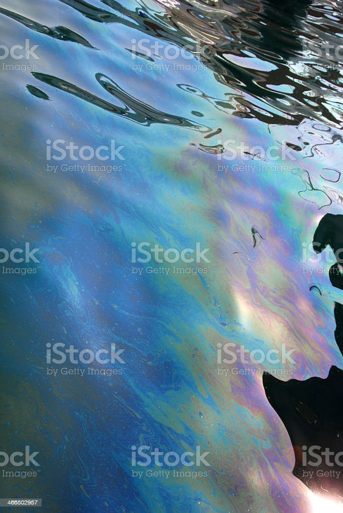 Blue and purple oil slick on black background royalty-free stock photo