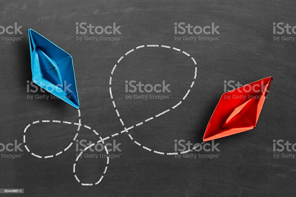 Blue and red paper boats connected with dots stock photo