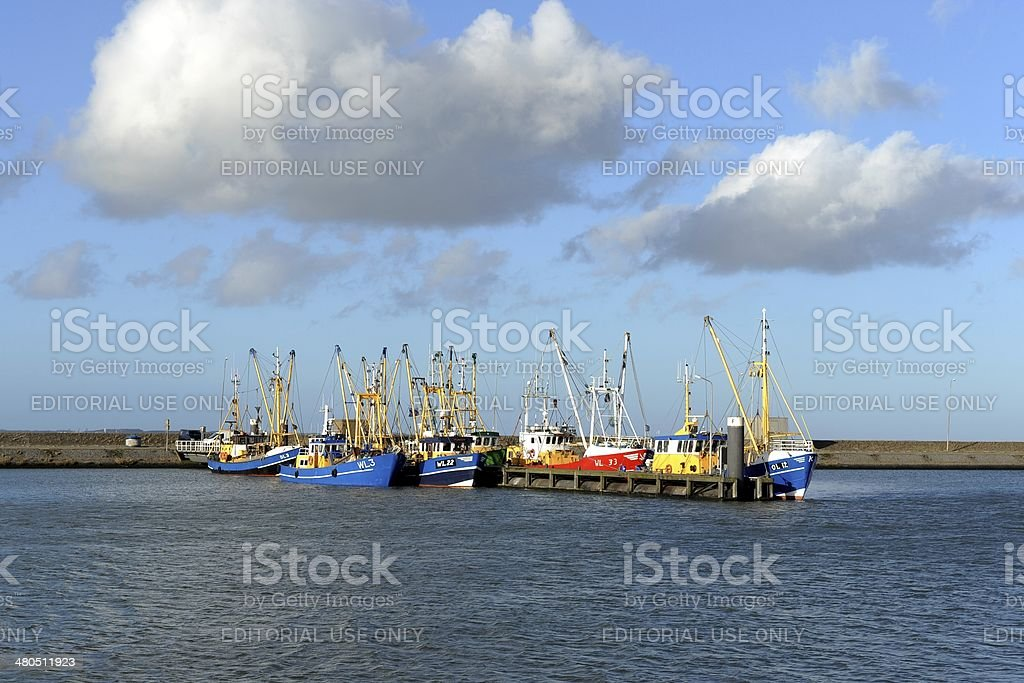 Blue and red ships in a fishing harbour stock photo