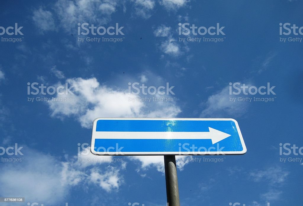 Blue and white arrow sign against sky stock photo