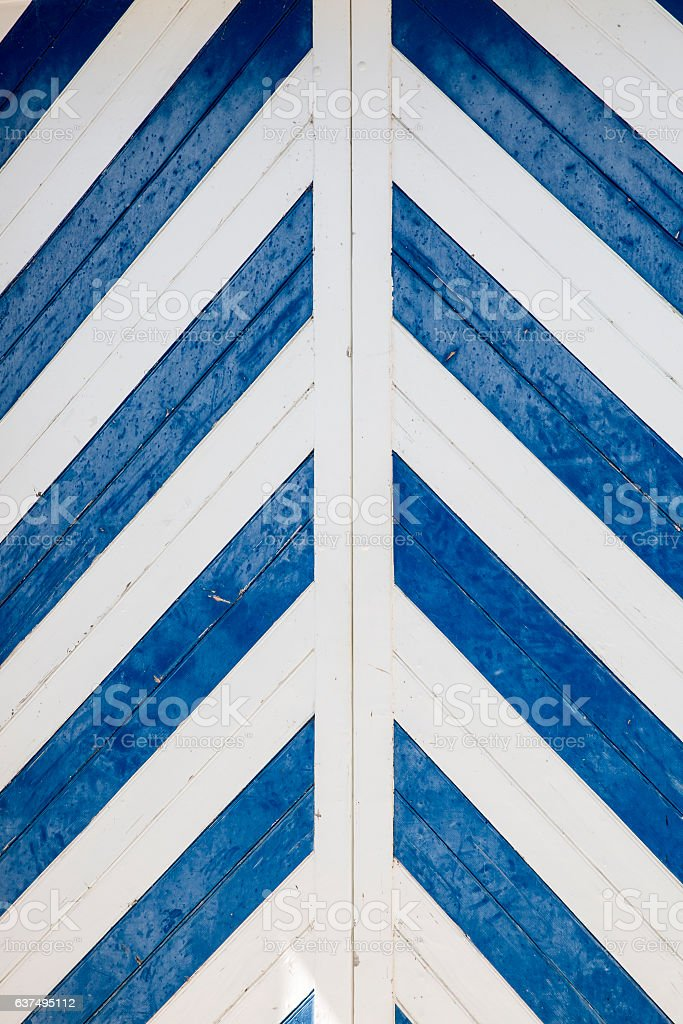 Blue and white chevron pattern on a wooden door stock photo
