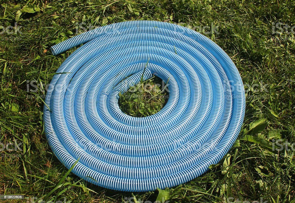 Blue and white corrugated plastic hose on green grass stock photo