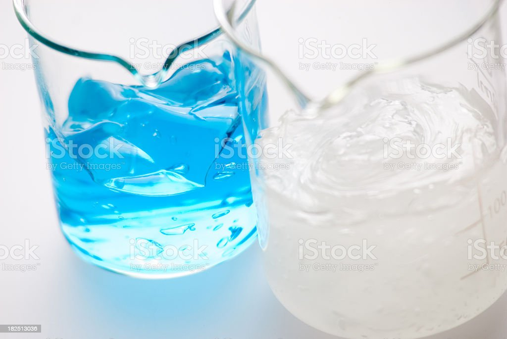 Blue and white gels separated in two measuring beakers stock photo