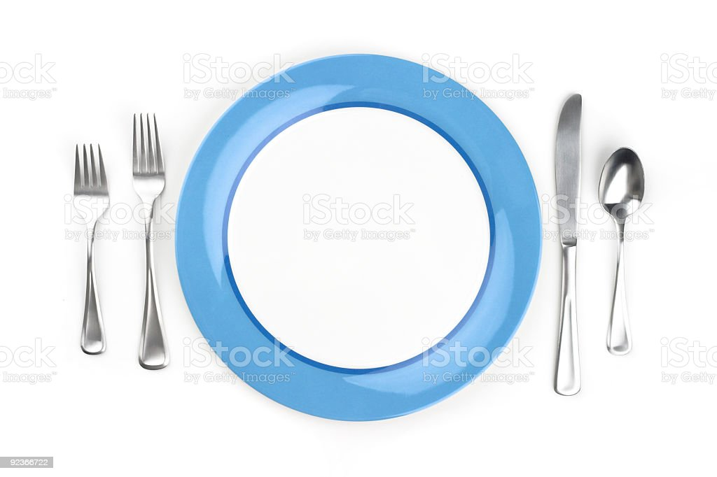 Blue and white plate with silver cutlery on either side royalty-free stock photo