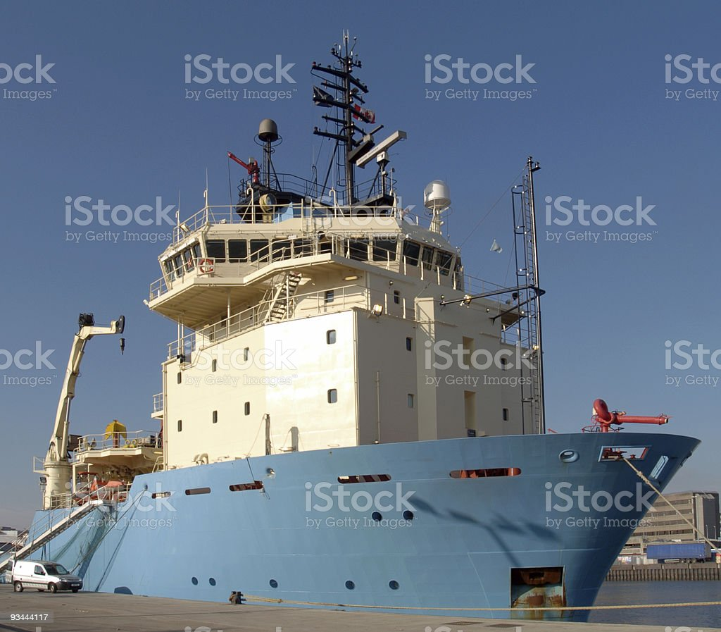 blue and white ship that support oil rigs stock photo