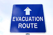 Blue and white sign with evacuation route on and arrow