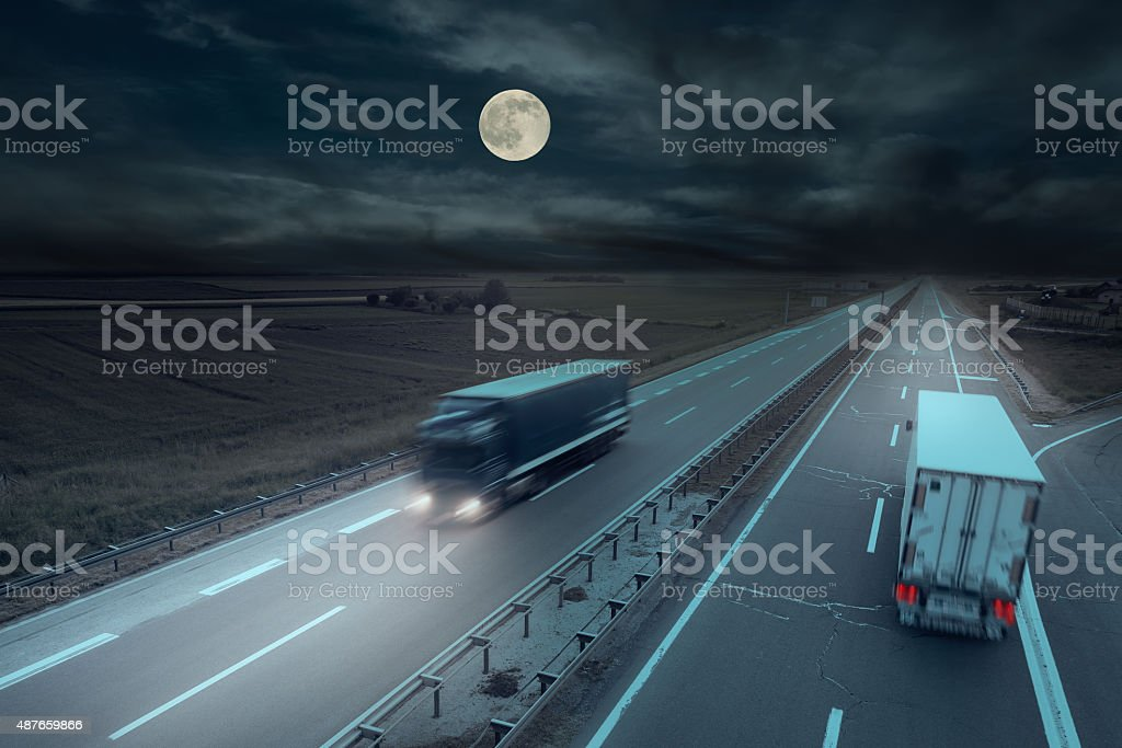 Blue and white truck in motion blur at midnight stock photo
