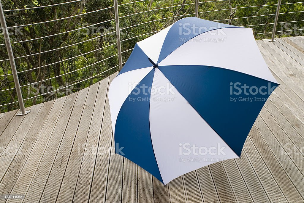 Blue and white Umbrella on a wooden deck. royalty-free stock photo