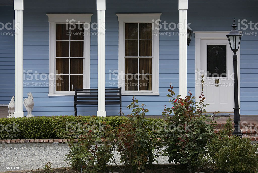 Blue and white Victorian with bench on porch stock photo