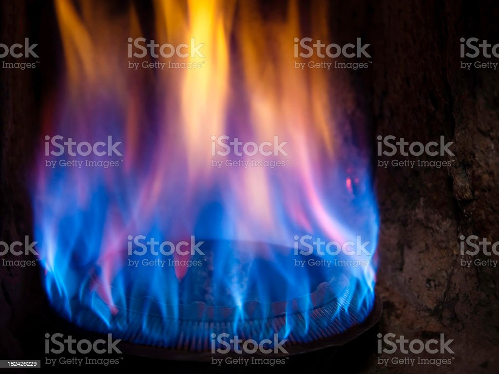 Blue and yellow flames on a gas burner stock photo