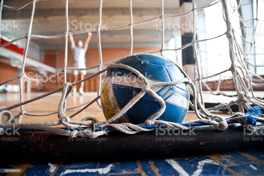 Blue and yellow handball inside of goal net stock photo