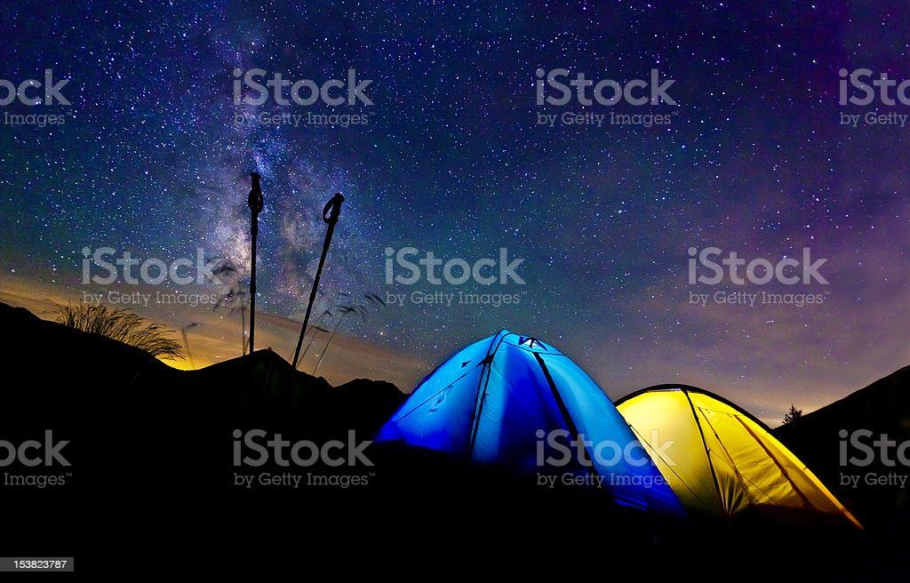 Blue and yellow tents on a dark hill under the Milky Way royalty-free stock photo