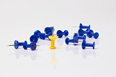 Blue and yellow thumbtacks on a white background.