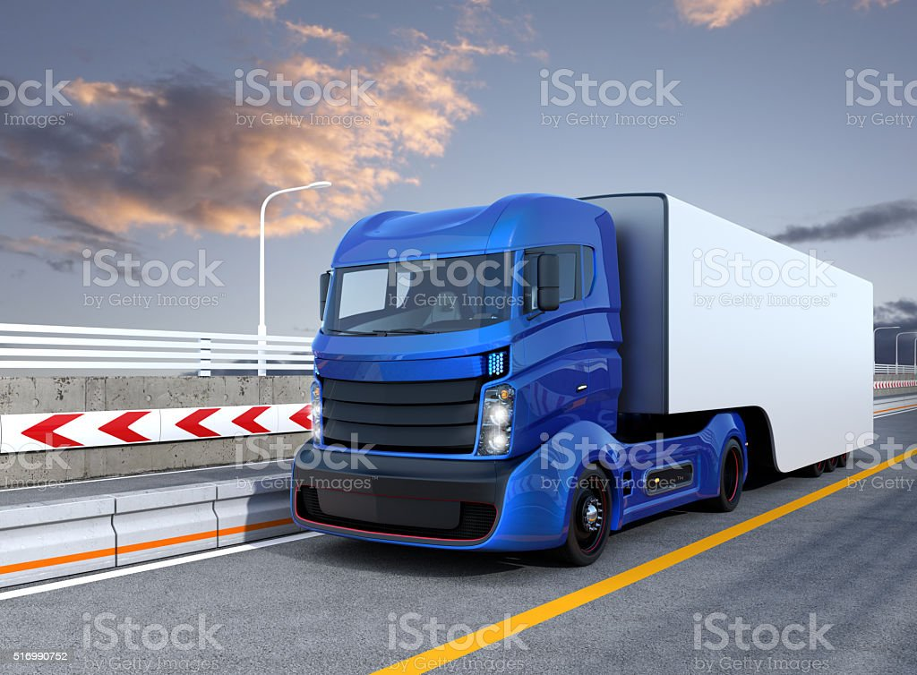 Blue autonomous hybrid truck driving on highway stock photo