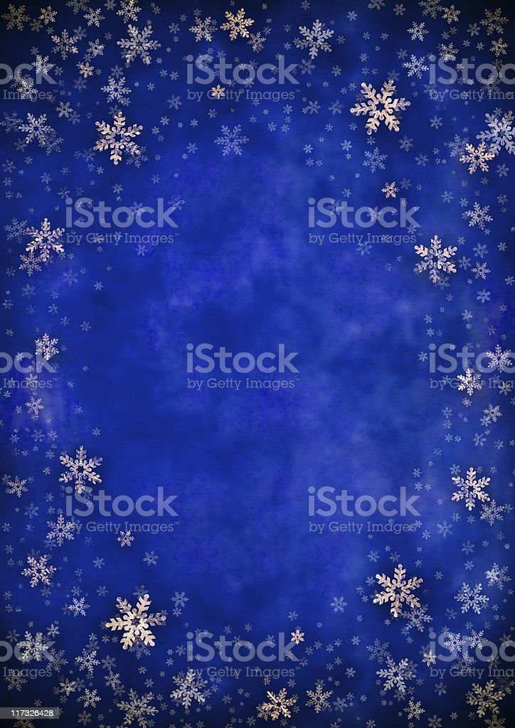 Blue background vignetted with gold foil snowflakes stock photo
