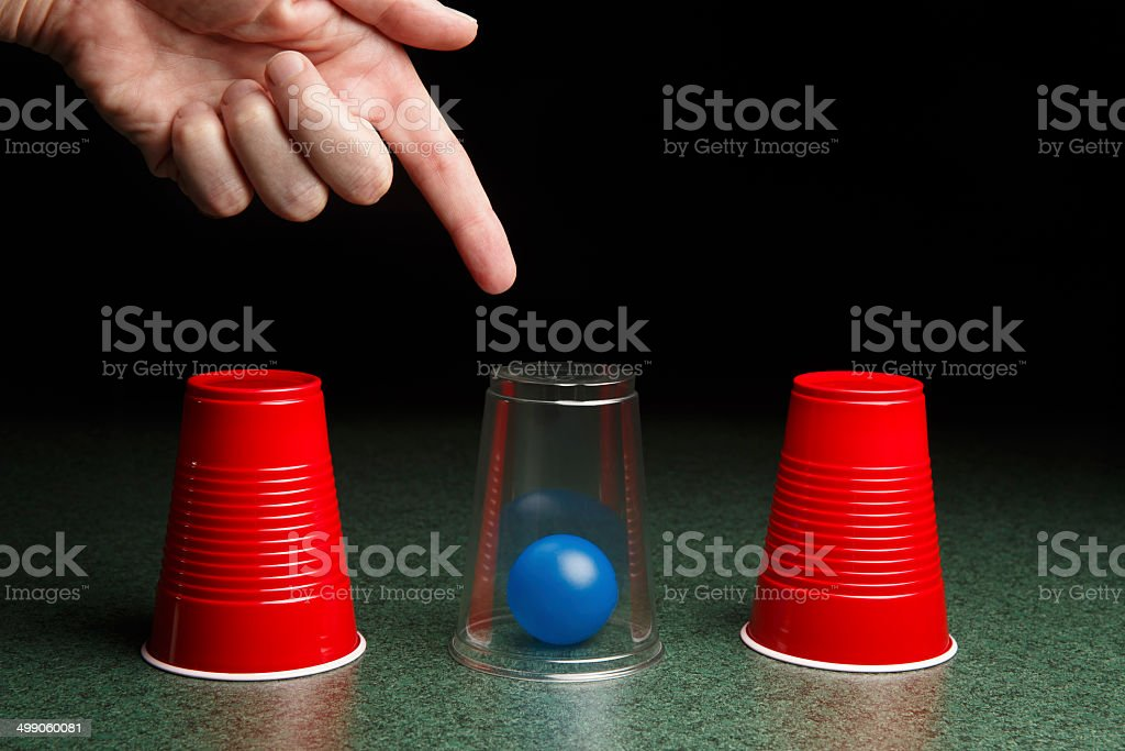 Blue Ball Under Clear Cup with Hand stock photo