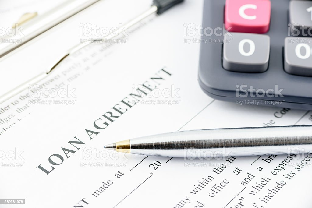 Blue ballpoint pen and a calculator on a loan agreement. stock photo