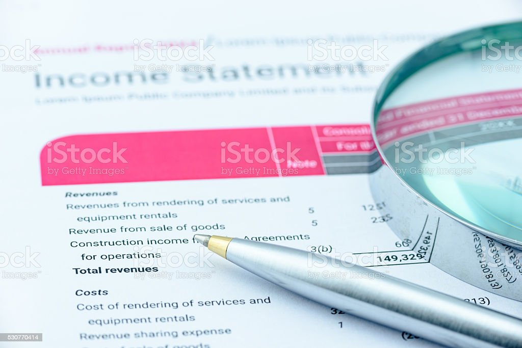 Blue ballpoint pen and a magnifier on an income statement. stock photo