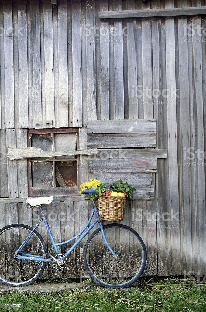 A blue bicycle leaning against a tin house stock photo