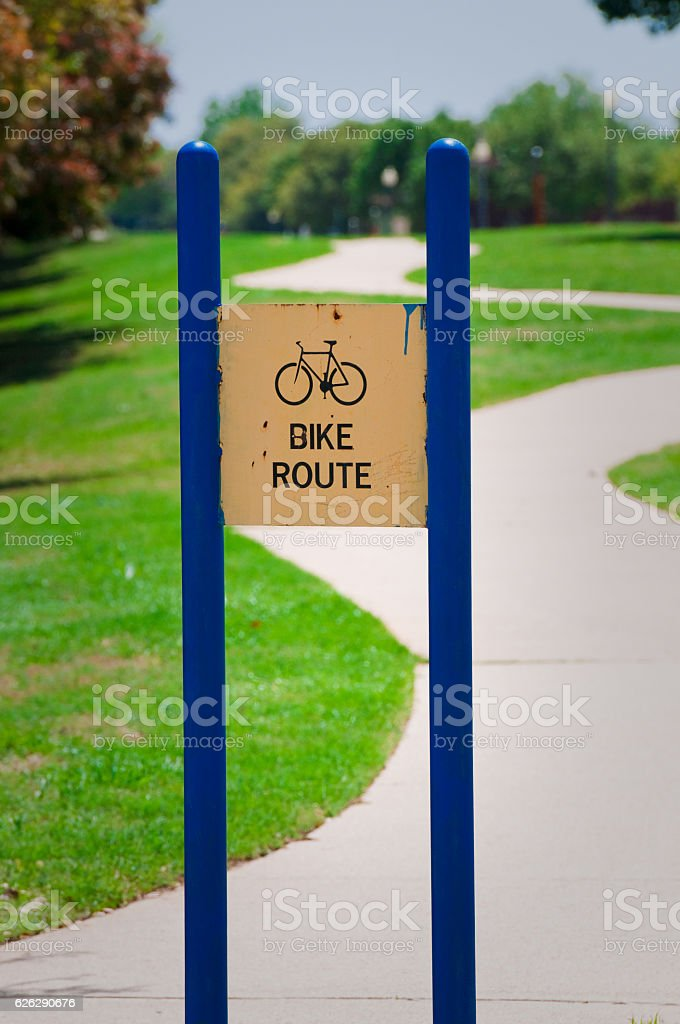 Blue bike route sign in front of sidewalk stock photo